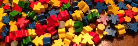 A haphazard pile of meeples - roughly human-shaped game pieces - in assorted colors