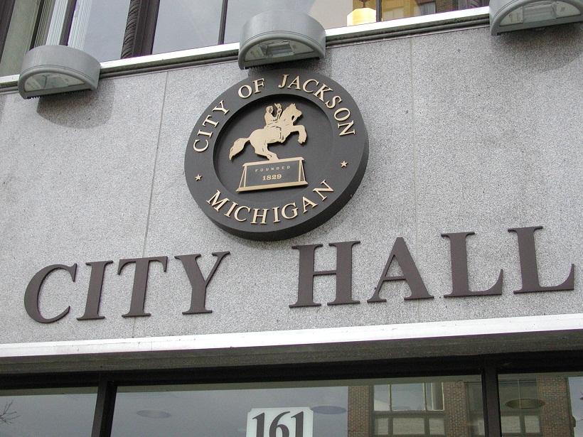 "A picture of the front of the Jackson, MI city hall, focusing on the seal of the city which is a man riding a horse that is rearing up on its hind legs and circumnavigated by the text ""City of Jackson - Michigan"""